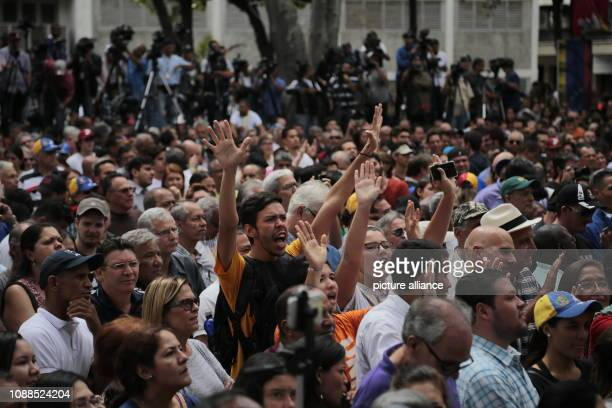 Numerous demonstrators raise their hands in support of the selfproclaimed interim president Guaido at a rally of the opposition in the Venezuelan...