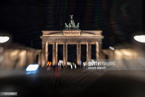 January 2020, Berlin: Tourists stand in front of the Brandenburg Gate late in the evening. Photo: Paul Zinken/dpa