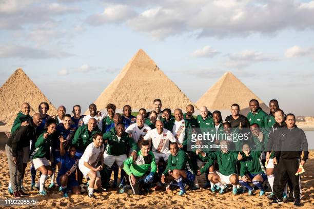 Members of the CAF and FIFA Legends teams pose in front of the Giza Pyramids after an exhibition match ahead of the CAF awards 2019 The CAF awards...