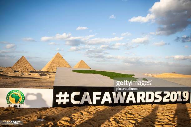 A banner of the 2019 CAF Awards hangs from a platform in front of the pyramids of Giza on which a grassy area with the outlines of the continent of...