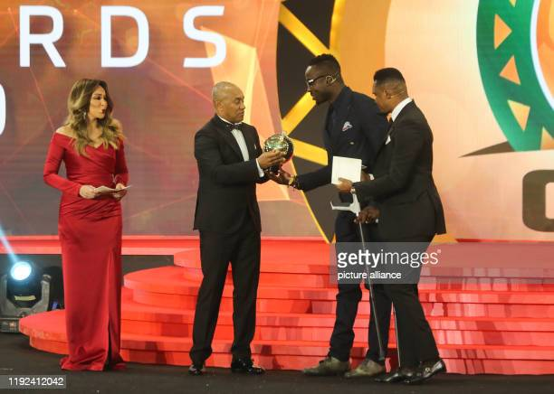 CAFPresident Ahmad Ahmad presents a special award to Kodjovi Obilale a former Togolese goalkeeper who was injured in a terrorist attack in 2010...