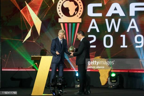 President of the Algerian Football Federation kheiredine Zetchi receives the the Men's Team of the Year award from French football manager Arsene...