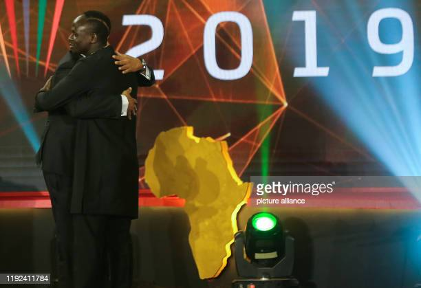 Senegalese footballer Sadio Mane embraces Former Cameroonian footballer Samuel Eto'o after receiving the Player of the Year award during the 2019 CAF...
