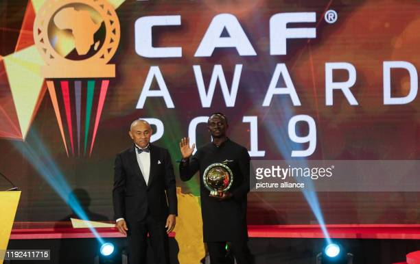 Senegalese footballer Sadio Mane receives the Player of the Year award from CAFPresident Ahmad Ahmad during the 2019 CAF Awards ceremony at Albatros...