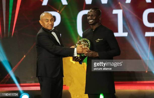 Senegalese footballer Sadio Mane receives the Player of the Year award from CAF President Ahmad Ahmad during the 2019 CAF Awards ceremony at Albatros...