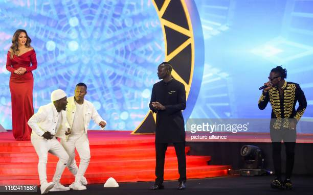 Senegalese footballer Sadio Mane stands with performers after receiving the Player of the Year award during the 2019 CAF Awards ceremony at Albatros...