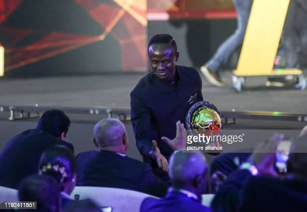 Senegalese footballer Sadio Mane winner of the Player of the Year award shakes hands with CAF President Ahmad Ahmad during the 2019 CAF Awards...