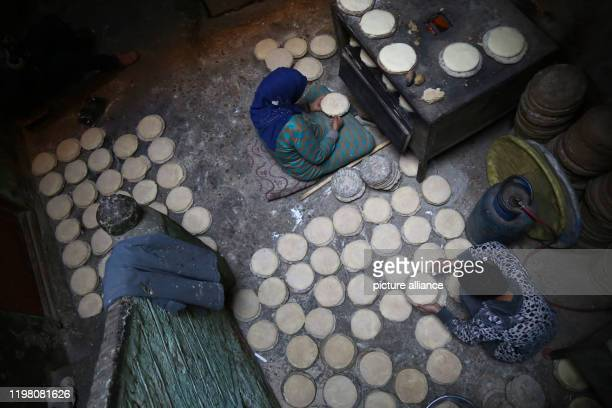 "January 2020, Egypt, Manfalut: A picture provided on 02 February 2020 shows women baking Sun Bread, known in local dialect as ""Eish Shamsi"", a thick..."
