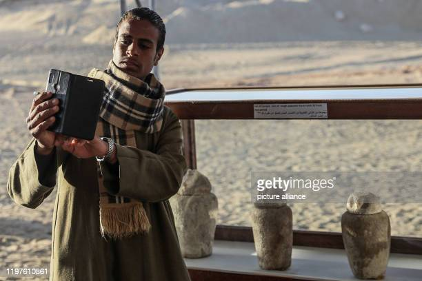 January 2020, Egypt, Minya: A man takes a selfie with artifacts found in one of three newly discovered communal tombs of the high priests of ancient...