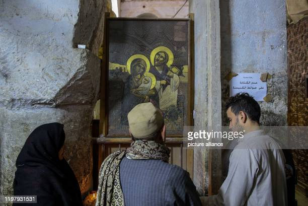 January 2020, Egypt, Minya: People place candles inside the Virgin Mary church at Gabal et-Tayr Monastery, as the renovation process continues for...
