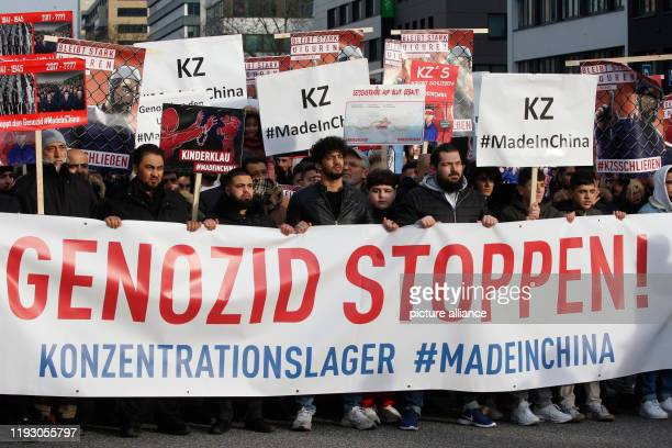 """January 2020, Hamburg: Behind a banner with the inscription """"Stop Genocide! Concentration camp #MadeinChina"""" people demonstrate against the..."""