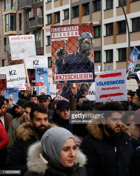 January 2020, Hamburg: People demonstrate against the oppression of the Uighur Muslim minority in China. On one of the posters, the image of a Muslim...