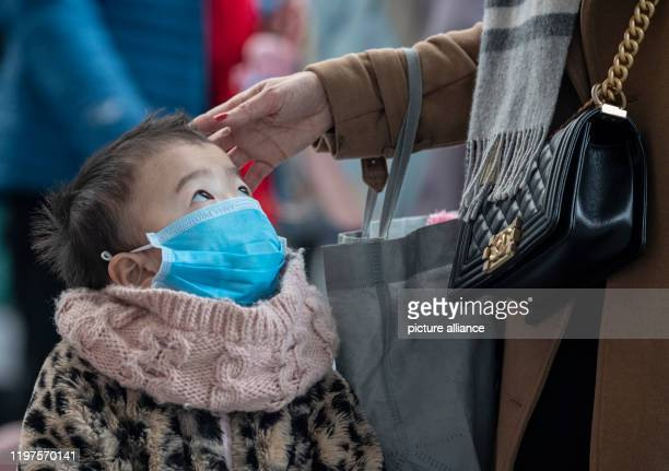 Together with her mother little Tramy is waiting at the checkin counter of a Vietnamese airline at Frankfurt Airport She wears a face mask For fear...
