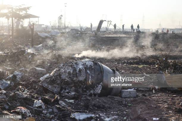 January 2020, Iran, Shahedshahr: Debris of an aircraft lay at the scene, where a Ukrainian airplane carrying 176 people crashed on Wednesday shortly...