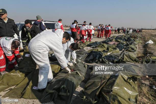 Rescue workers and forensic investigators inspect the bodies of victims of a Ukrainian plane crash A Ukrainian airplane carrying 176 people crashed...