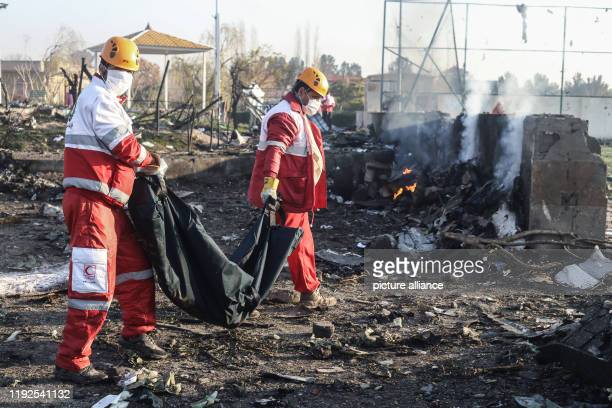 Rescue workers carry the body of a victim of a Ukrainian plane crash A Ukrainian airplane carrying 176 people crashed on Wednesday shortly after...