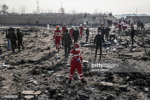 January 2020, Iran, Shahedshahr: Rescuers search debris at the scene, where a Ukrainian airplane carrying 176 people crashed on Wednesday shortly...