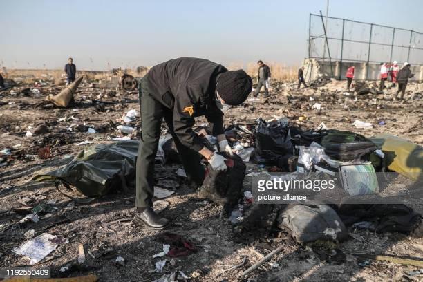 January 2020, Iran, Shahedshahr: Rescuers search the debris at the crash site. A Ukrainian passenger plane has crashed near the Imam Khomeini airport...