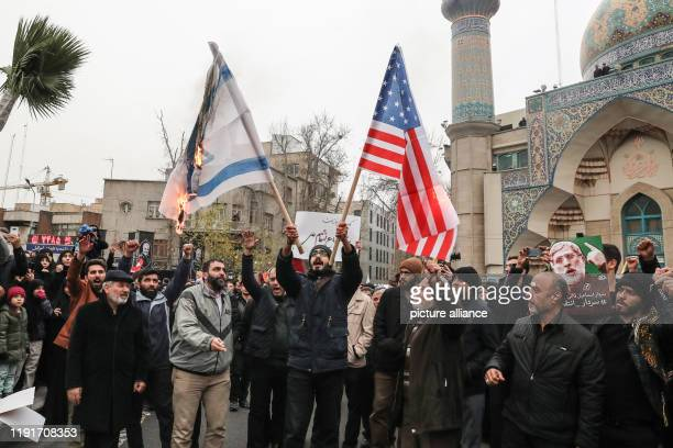 January 2020, Iran, Tehran: Iranians burn the US and the Israeli flags during a mourning rally at Felestin Square in honour of Qassem Soleimani,...