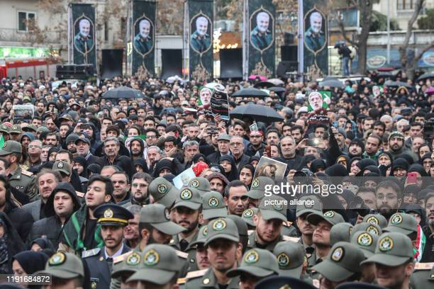 January 2020, Iran, Tehran: Members of the Iranian military join people as they take part in a mourning rally at Felestin Square in honour of Qassem...
