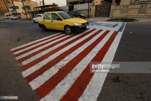 January 2020, Iraq, Baghdad: A car drives over the USand the Israeli flags, painted on a road in Baghdad in the aftermath of a US airstrike that...