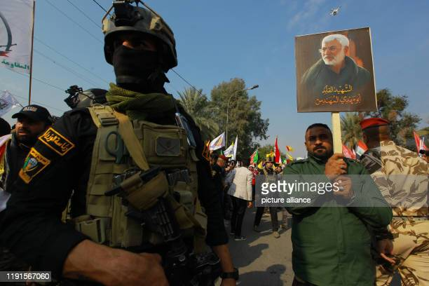 January 2020, Iraq, Baghdad: A man hold the picture of Abu Mahdi al-Mohandes stands next to an Iraqi security member during a funeral procession for...
