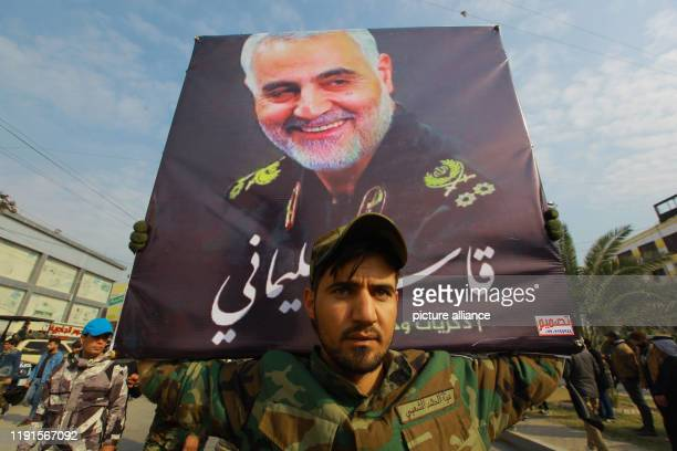 A man holds Qassem Soleimani picture during a funeral procession for Qassem Soleimani the commander of Iran's elite Quds Force and Abu Mahdi...