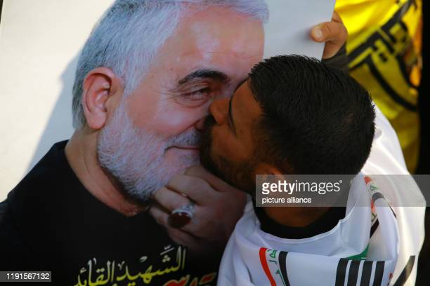 January 2020, Iraq, Baghdad: A man kisses Qassem Soleimani's picture during a funeral procession for Qassem Soleimani, the commander of Iran's elite...