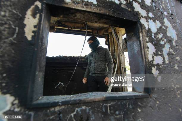 January 2020, Iraq, Baghdad: A protester stands inside a burned checkpoint during the sit-in against deadly US airstrikes on sites of a Shiite...