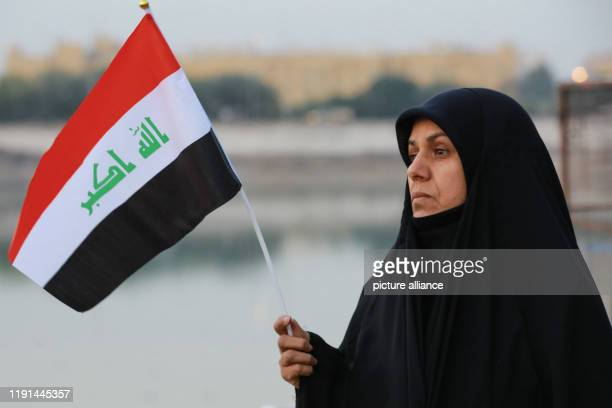 January 2020, Iraq, Baghdad: An woman waves the Iraqi flag during an anti-US protest by supporters of the predominantly Shia Muslim Popular...