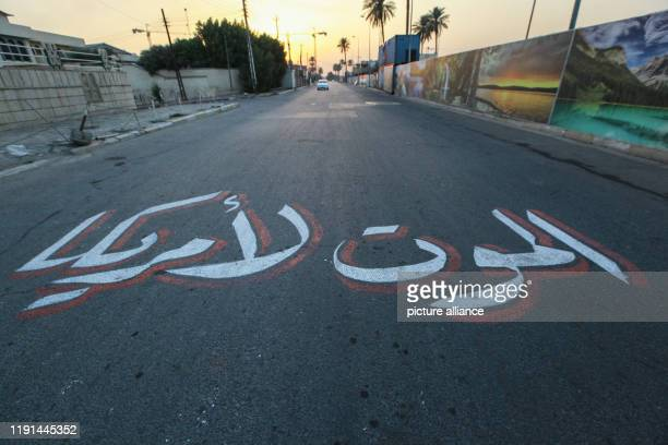"""January 2020, Iraq, Baghdad: """"Death to America"""" is seen written in Arabic on a road nearby the US embassy in Baghdad in the aftermath of a US..."""
