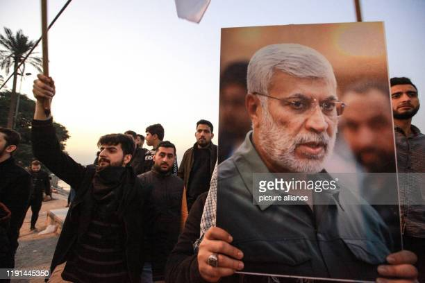 January 2020, Iraq, Baghdad: Supporters of the predominantly Shia Muslim Popular Mobilization Forces gather with flags and posters of the PMF deputy...