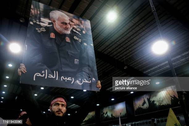 January 2020, Lebanon, Beirut: Asupporter of Lebanon's Iran-allied Hezbollah movement, holds a picture of Qassem Soleimani, commander of the elite...