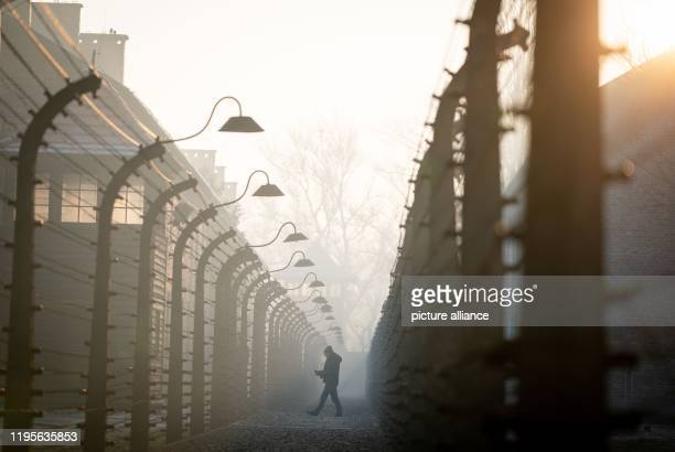 January 2020, Poland, Oswiecim: Early in the morning, a man walks through the barbed wire facility of the former Auschwitz I concentration camp....
