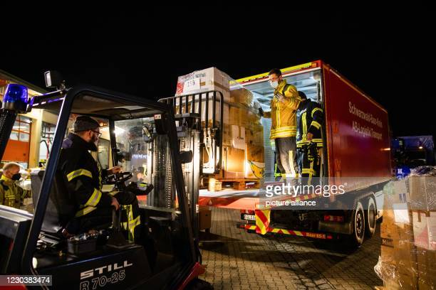 January 2021, Baden-Wuerttemberg, Bad Krozingen: Firefighters load a pallet of relief supplies onto a truck. Following an appeal, fire brigades from...