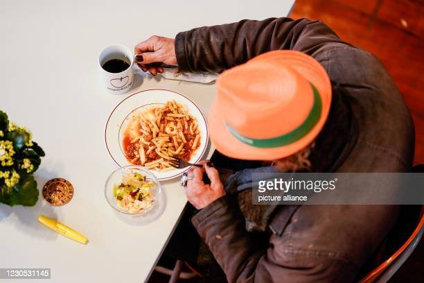 January 2021, Baden-Wuerttemberg, Mannheim: A man sits at a table in the CityKirche Konkordien at the start of the Vesperkirche under Corona...