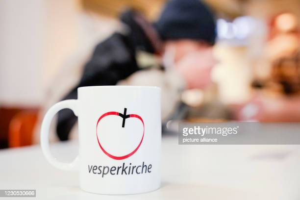 """January 2021, Baden-Wuerttemberg, Mannheim: Behind a cup with the inscription """"Vesperkirche"""", a man eats a meal under Corona conditions at the..."""