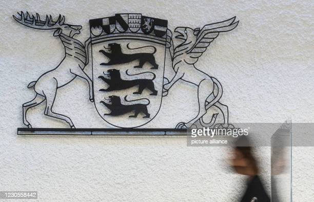 January 2021, Baden-Wuerttemberg, Stuttgart: A court aide walks past a coat of arms of the state of Baden-Württemberg in Room 1 of Stuttgart Regional...
