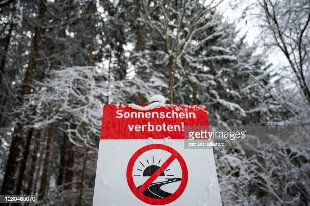 "January 2021, Baden-Wuerttemberg, Weil im Schönbuch: A sign reading ""Sunshine forbidden!"" stands in the snow in a parking lot at the Schönbuch Nature..."