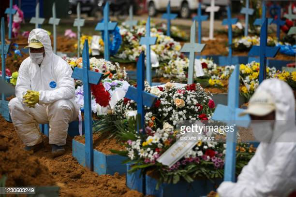 January 2021, Brazil, Manaus: Cemetery workers in protective suits sit on graves decorated with flowers during a funeral at Nossa Senhora Aparecida...