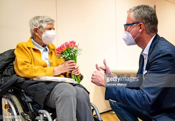 January 2021, Hamburg: After her second Corona vaccination, 84-year-old Karin Sievers receives a bouquet of flowers from Frank Schubert, chairman of...