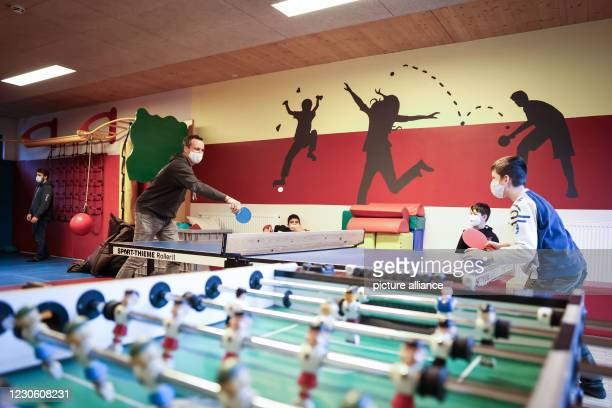 January 2021, Hamburg: Tobias Lucht, regional director of Arche Hamburg, plays table tennis with three boys in the sports room of the Arche...