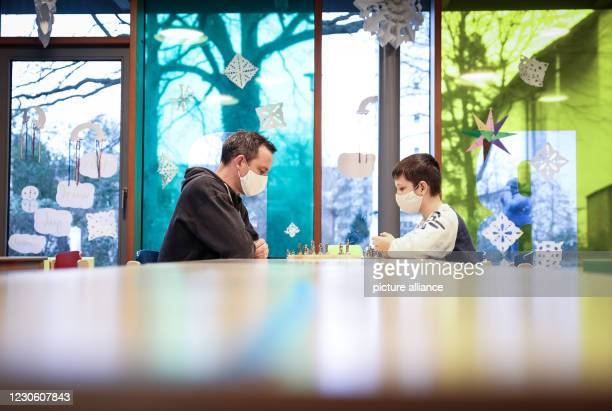 January 2021, Hamburg: Tobias Lucht , Regional Manager Arche Hamburg, plays chess with Darius in the rooms of the Arche children's project in...