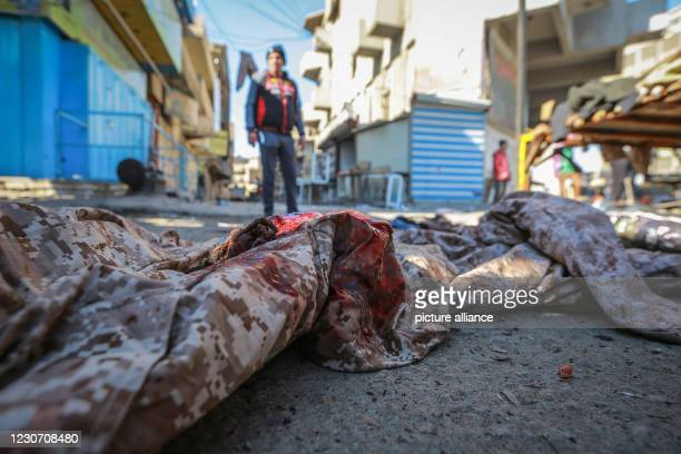 January 2021, Iraq, Baghdad: A sheet stained with the blood is seen at the scene of a twin suicide attack in a street market selling used clothes in...