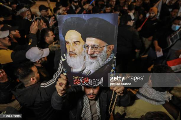 January 2021, Iraq, Baghdad: Iraqi man carries a poster of the Ayatollahs Khamenei and Khomeini as he commemorate the one-year anniversary of the...