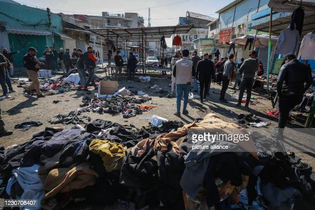 January 2021, Iraq, Baghdad: Iraqi vendors inspect the scene of a twin suicide attack in a street market selling used clothes in central Baghdad. At...