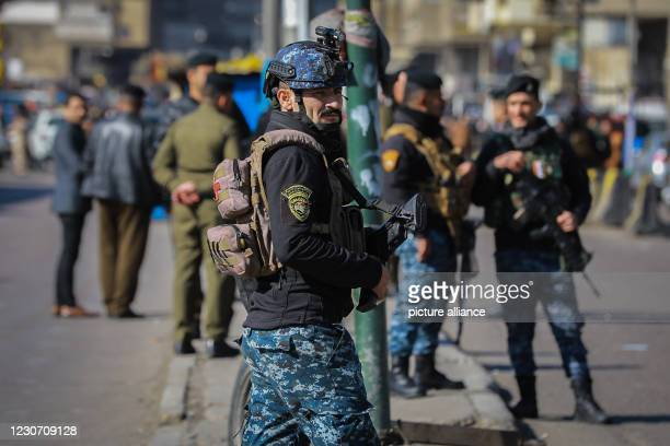 January 2021, Iraq, Baghdad: Members of Iraqi security forces stand at the scene of a twin suicide attack in a street market selling used clothes in...