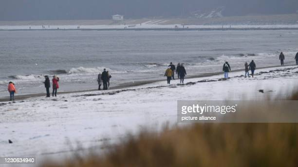 January 2021, Mecklenburg-Western Pomerania, Zinnowitz: Walkers walk on a lightly snow-covered beach on the island of Usedom . Due to further high...