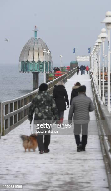 January 2021, Mecklenburg-Western Pomerania, Zinnowitz: Walkers walk on the pier in the Baltic Sea resort in the district of Vorpommern-Greifswald....
