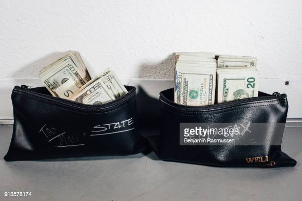 BOULDER COLORADO USA – January 23 2015 Dylan Donaldson sorts money to be set aside for sales tax in the Karing Kind marijuana dispensary which he...